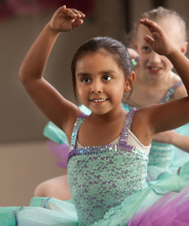 girl in green and purple ballet costume, arms raised